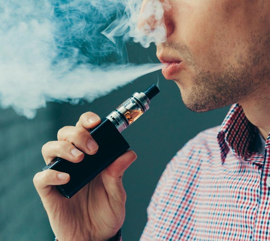 Mann dampft mit E-Zigarette